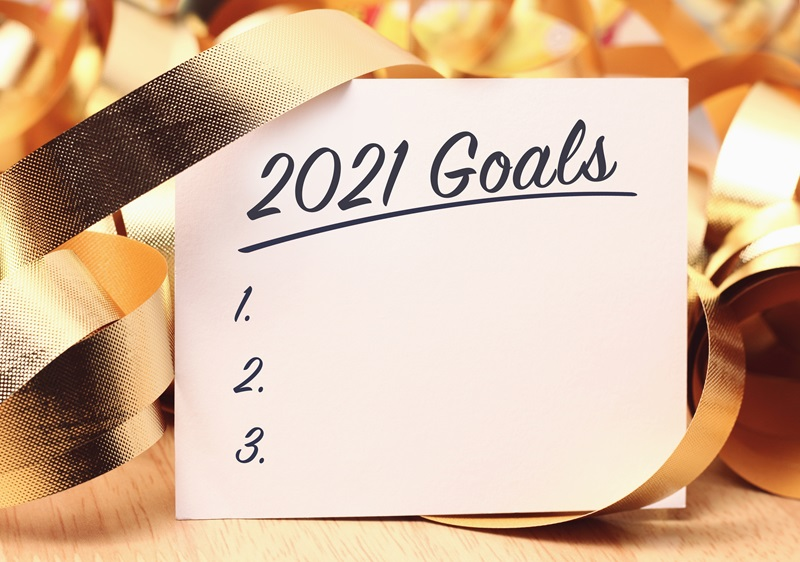Text 2021 Goals with a blank list written on a note on a festive background